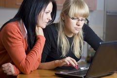 Dos mujeres en la computadora portátil Foto de archivo libre de regalías