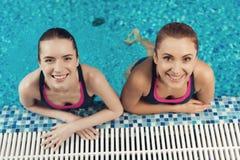 Dos mujeres en la frontera de la piscina en el gimnasio Mirada de la mamá y de la hija feliz, de moda y apta foto de archivo libre de regalías