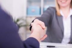 Dos mujeres en la oficina que tiene un acuerdo y que sacude las manos fotografía de archivo