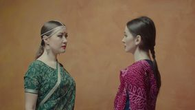 Dos mujeres en la sari que mira en ojos de cada uno almacen de video