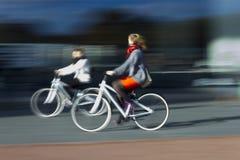Dos mujeres en las bicis borrosas en perfil Foto de archivo libre de regalías