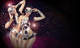 Dos mujeres en los trajes teatrales de moda que bailan sobre fondo abstracto Imagen de archivo libre de regalías