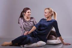 Dos mujeres en pijamas se sientan en las almohadas en un fondo gris Imagenes de archivo