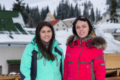 Dos mujeres en trajes de esquí y con las gafas del esquí que colocan nieve-covere Fotografía de archivo libre de regalías