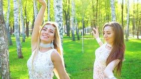 Dos mujeres en trajes y accesorios del encanto bailan en arboleda iluminada por el sol del abedul almacen de video