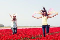 Dos mujeres en un campo rojo del tulipán Foto de archivo libre de regalías