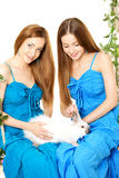 Dos mujeres en un oscilación en el fondo blanco Foto de archivo