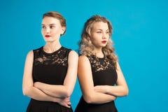 Dos mujeres en vestidos idénticos están enojadas en uno a Fotografía de archivo libre de regalías