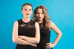 Dos mujeres en vestidos idénticos están enojadas en uno a Imagenes de archivo