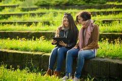 Dos mujeres encantadoras jovenes se sientan en los pasos de piedra con la tableta en manos Foto de archivo