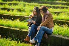 Dos mujeres encantadoras jovenes se sientan en los pasos de piedra con la tableta en manos Imagen de archivo