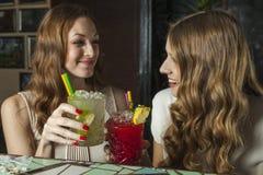 Dos mujeres encantadoras que beben los cócteles en una barra Fotos de archivo libres de regalías