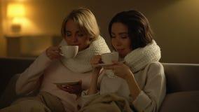 Dos mujeres enfermas que beben té caliente y la sonrisa, sintiendo mejor después del tratamiento almacen de metraje de vídeo