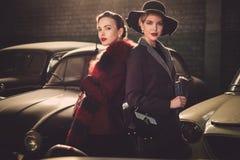 Dos mujeres entre los coches retros en garaje Foto de archivo libre de regalías