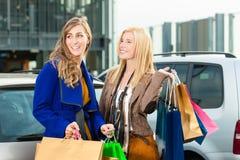 Dos mujeres eran compras y conducción a casa foto de archivo libre de regalías