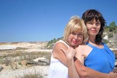 Dos mujeres están abrazando Fotos de archivo libres de regalías