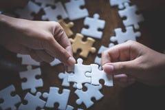 Dos mujeres están intentando conectar un par de pedazos del rompecabezas Símbolo de la asociación y de la conexión Concepto de es foto de archivo libre de regalías