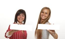Dos mujeres están llevando a cabo una muestra blanca en blanco. imágenes de archivo libres de regalías