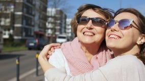 Dos mujeres están sonriendo, retrato en una calle de la ciudad Mujeres brillantes del sol del verano, mayores y jovenes con los v almacen de video