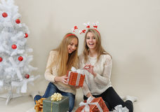 Dos mujeres felices con las cajas de regalo abren una de ellas Foto de archivo
