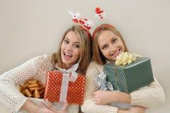 Dos mujeres felices con las cajas de regalo que miran la cámara Foto de archivo