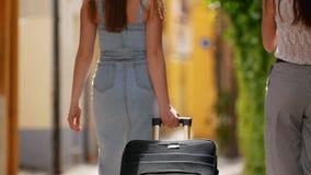 Dos mujeres felices jovenes con el equipaje que va al callejón de la ciudad italiana metrajes
