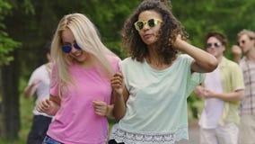 Dos mujeres felices jovenes que bailan a la música en el partido, individuos que disfrutan de verano en parque metrajes