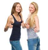 Dos mujeres felices jovenes que muestran el pulgar encima de la muestra Foto de archivo libre de regalías