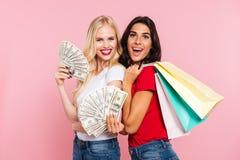 Dos mujeres felices que presentan con el dinero y los paquetes Foto de archivo libre de regalías