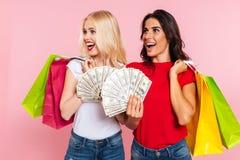 Dos mujeres felices que presentan con el dinero y los paquetes Imagen de archivo libre de regalías