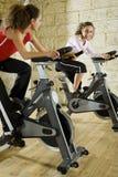Dos mujeres felices que se resuelven en las bicis de ejercicio Fotos de archivo