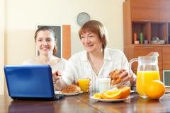 Dos mujeres felices que usan el ordenador portátil durante el desayuno Fotografía de archivo