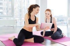 Dos mujeres felices que usan la tableta que se sienta en estudio de la yoga Foto de archivo