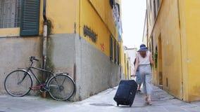 Dos mujeres felices que viajan jovenes que caminan con un equipaje en el fondo de paredes amarillas almacen de metraje de vídeo