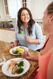 Dos mujeres gordas en dieta que comen la comida sana en cocina Imagen de archivo