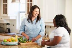 Dos mujeres gordas en la dieta que prepara verduras en cocina Imagenes de archivo