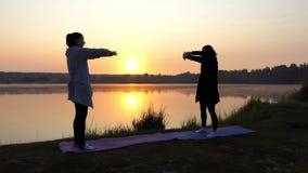 Dos mujeres hacen ejercicios de respiración de la yoga en la puesta del sol Neas un lago almacen de video