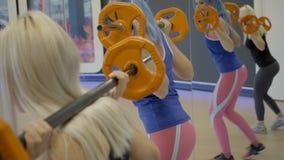 Dos mujeres hacen estocadas con el peso libre en club de deportes almacen de metraje de vídeo