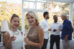 Dos mujeres hermosas con los vidrios del champán que se colocan en restaurante Imágenes de archivo libres de regalías