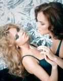Dos mujeres hermosas en la ropa interior que abraza en el sofá Fotografía de archivo