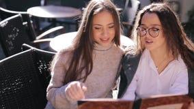 Dos mujeres hermosas jovenes que miran el menú en restaurante, páginas de torneado y eligiendo las placas para el desayuno almacen de video