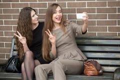 Dos mujeres hermosas jovenes que toman un selfie en la calle Imagen de archivo libre de regalías