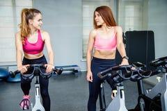 Dos mujeres hermosas, llevando en la ropa de deportes, haciendo ejercicio biking interior foto de archivo libre de regalías