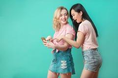 Dos mujeres hermosas multiétnicas asiático y selfie que toma caucásico en el estudio Imagen de archivo libre de regalías