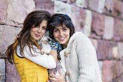 Dos mujeres hermosas que abrazan su pequeño perro al aire libre Fotografía de archivo