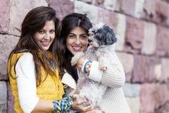 Dos mujeres hermosas que abrazan su pequeño perro al aire libre Fotos de archivo