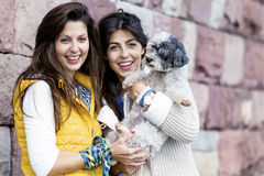 Dos mujeres hermosas que abrazan su pequeño perro al aire libre Foto de archivo libre de regalías