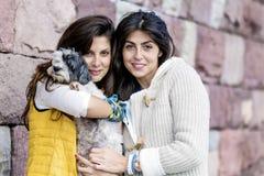Dos mujeres hermosas que abrazan su pequeño perro al aire libre Fotos de archivo libres de regalías