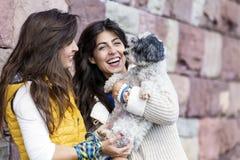 Dos mujeres hermosas que abrazan su pequeño perro al aire libre Imagen de archivo