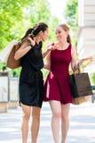 Dos mujeres hermosas que buscan boutiques de la moda durante compras Fotos de archivo libres de regalías